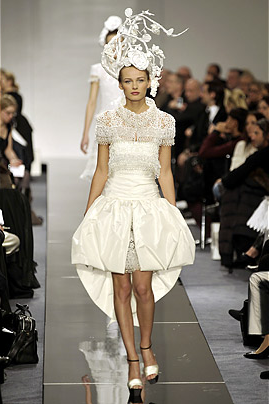 Karl Lagerfeld's brilliant collection for Chanel was inspired by white paper and featured intricately sculpted paper hats hats by renowned Japanese hairstylist Katsuya Kamo. Models in short, structured dresses wore the paper hats in a room draped in laser-cut paper medallions, tablecloths and garlands.